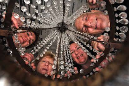 "The Nierman family from left: daughter Claire Niermann; mother, Eleanor McKay, daughter, Eleanor Niermann, and father, Joe Niermann, are pictured through a ""Campaign"" chandelier which they designed and produced.They run the family-owned business, Niermann Weeks which makes custom traditional and contemporary furnishings, and custom-made chandeliers. They also sell non-custom furniture to designer showrooms in the US and Canada. NOTE: The ""Campaign"" chandelier is one that collapses onto itself for easy traveling. This style of chandelier was used in war time for easy traveling from one war zone to the next."