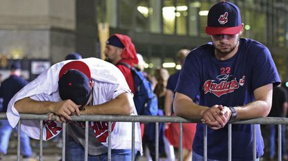 Cleveland Indians fans Levi Jones, left, and Kyle Zabarsky react during a watch party, after Game 7 of the baseball World Series between the Indians and the Chicago Cubs, outside Progressive Field, early Thursday, Nov. 3, 2016, in Cleveland. The Cubs won 8-7 to win the series.