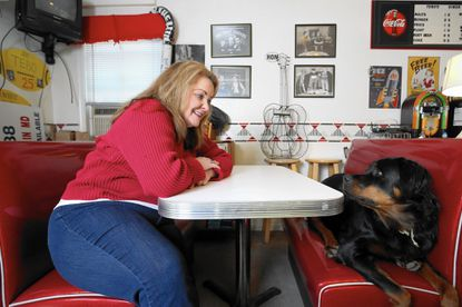 Bettina Tebo, the new president of the Arbutus Business and Professional Association, poses for a photo with her dog, Abigayle, in her home office.