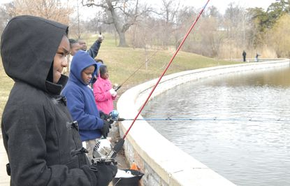 The Spring Fishing Rodeo at the Patterson Park Boat Lake was held March 28, 2015, despite temperatures in the lower 30s with some snow. Erica Wiggins, 11 (LT: black jacket), her cousin Adrian Wiggins, 9 (second LT: blue jacket), and Erica's sister Deionnie Wiggins, 8 (third LT: pink jacket) were hoping to catch catfish.
