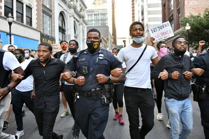 Baltimore Officer Odis Daniels, center, marching arm-in-arm with Shawn Mackey at left, and Jonathan Davidson, second from right, was one of two police officers who linked arms and later took a knee with the marchers at the conclusion of the Wednesday evening Black Lives Matter march in downtown Baltimore. June 3, 2020. (Amy Davis/Baltimore Sun)