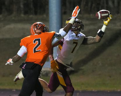 Essex, MD -- 11/13/2015 -- Dunbar Poets wide receiver Dae'lun Darien (7) makes a one-handed catch for a touchdown in front of Eastern Tech Mavericks safety Prince Ajegwu (2) in the Class 2A North football semifinal at CCBC Essex on Nov. 13, 2015.