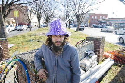 """Andreas """"Spilly"""" Spiliadis leans against the Waverly sign in the median overlooking the 32nd Street Farmers' Market on Feb. 25. Spiliadis can be found most Saturday morning hula-hooping in the median. Now, he is off to Rome, Italy to compete in a big hula-hoop competition."""