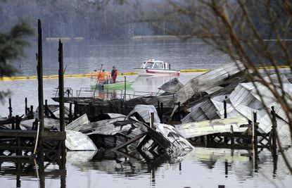 People on boats patrol near the charred remains of a dock following a fatal fire at a Tennessee River marina in Scottsboro, Ala., on Jan. 27, 2020.