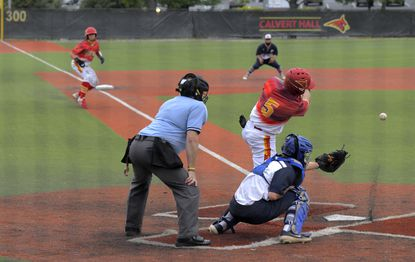 Calvert Hall Cardinals batter Jannuel Wispi Rhodes (5) hits a chopper against the Gilman Greyhounds that winds up scoring Jake Butler from third (left) and John Harris from second during the first inning.