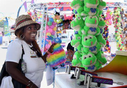 Martha Swann of Towson chose a rainbow llama for winning a water gun game at the Maryland State Fair.