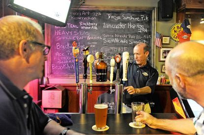 Bartender Marty Fisher fills a customer's beer jug with one of the 14 drafts available at the Baltimore Taphouse in Canton.