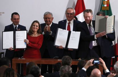 Mexico's Treasury Secretary Arturo Herrera, left, Deputy Prime Minister of Canada Chrystia Freeland, second left, Mexico's President Andres Manuel Lopez Obrador, center, Mexico's top trade negotiator Jesus Seade, second right, and U.S. Trade Representative Robert Lighthizer, hold the documents after signing an update to the North American Free Trade Agreement, at the national palace in Mexico City, Tuesday, Dec. 10. 2019.