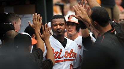 Orioles center fielder Adam Jones and third baseman Manny Machado, behind him, get high-fives in the dugout after they scored in the first inning.