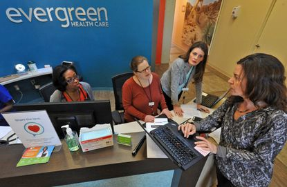 Staff at the Evergreen Health Care center at the Rotunda huddle to discuss patient care. The Evergreen Health Cooperative, which operates the clinic, is suing the federal government to stop or delay a risk adjustment payment that it says could compromise its future.