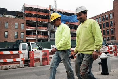 Men walk by a construction site in Brooklyn on June 5, 2015 in New York City. The government is releasing February's job report on March 10, 2017.