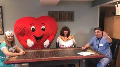 A screen grab from one of the videos filmed by Knollwood residents to encourage the community to get healthy and promote signups to the Towson Healthy Hearts 5K. From left: Marlene Riley, Stephanie Parry and Dave Riley discuss Chinese Carryout with Mr. Fancy Happy Heart (center).