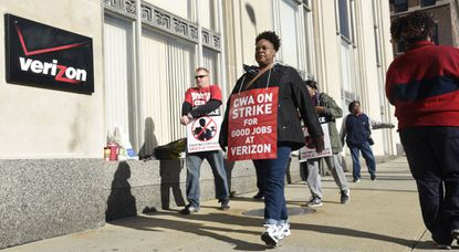 Verizon workers walk the picket line outside the Telephone Building at 320 St Paul Street. They have been working without a contract since August.