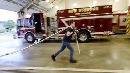 New Windsor Firefighter Matt Miziorko deploys hose during a training exercise at the New Windsor fire company Monday, May 21, 2018.