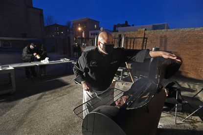 Chef Steven Allbright, right, culinary director at the Franciscan Center of Baltimore, checks on some of the 300 pounds of beef brisket for the center's marathon food giveaway Wednesday. Staff and volunteers distributed food throughout Baltimore City nonstop for a full 24 hours.