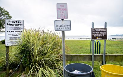 Signs warn of car towing and no public access to the community beach run by the Beverly Beach Community Association that is adjacent to Beverly-Triton Beach Park in Edgewater.