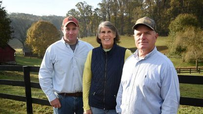 Local farmer John Rigdon, right, stands with his son, Harrison, and wife, Andrea, at the family farm in Jarrettsville. The Harford Soil Conservation District honored the Rigdons with the Conservation Farm of the Year award on Oct. 12.