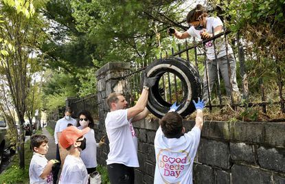 Erica Bloom, deputy director of Jewish Volunteer Connection, hands down a tire dumped in Hebrew Friendship Cemetery to Ross Goldstein and his son, Bram Goldstein, right. Ten volunteers from JVC cleaned up trash around the perimeter of the East Baltimore cemetery for the annual Good Deeds Day. Other volunteers helping, from left, are brothers Noah and Micah Bloom, and Susanna Garfein. April 7, 2021. (Amy Davis/Baltimore Sun).