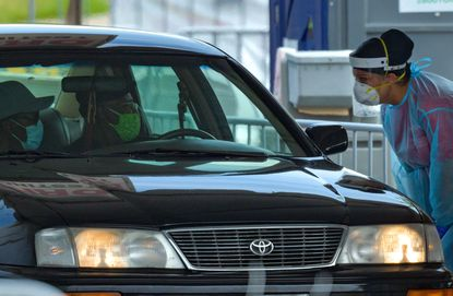 A car pulls through the drive-up COVID-19 testing site at Mondawmin Mall on Monday morning.