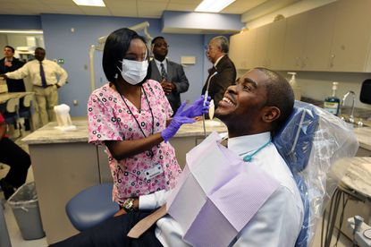 Shayla Thornton, a dental assistant student at Vivien T. Thomas Medical Arts Academy, gives a fluoride treatment to Christopher King, assistant vice principal for community health at MedStar Health.