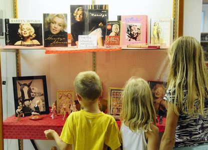 From left, Evan, Lauren and Grace Lapointe of Havre de Grace admire the items on display in the Marilyn Monroe exhibit at the Bel Air Llibrary, during a visit with their mom Thursday afternoon.
