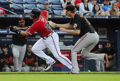 Baltimore Orioles pitcher Brian Matusz, right, tags out Atlanta Braves' Matt Diaz along the third base line on a single by shortstop Andrelton Simmons during the second inning of a baseball game on Friday, June 15, 2012, in Atlanta. (AP Photo/John Amis)