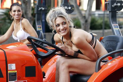 """Contestants Ashley I. (left) and Tandra get ready to race tractors on """"The Bachcelor."""""""