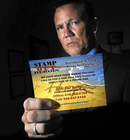 """Carroll County State's Attorney's Office's Drug Prevention and Treatment Liaison Tim Weber shows a new """"Stamp Out Heroin"""" card."""