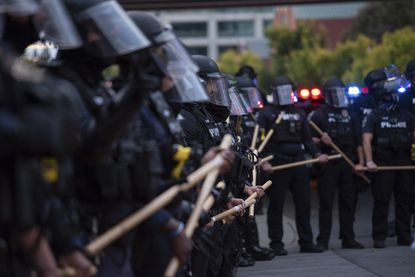 In this Sept. 25, 2020 photo, a line of police officers, ready to do battle, block protesters in Louisville, Kentucyy. (Isabel Miller via AP)