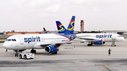 A member of Spirit Airlines grounds crew, right, guides a jet toward the runway.