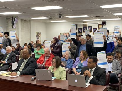 Members of the Muslim community stand in support of recognizing Muslim holidays in the Baltimore County Public Schools calendar.