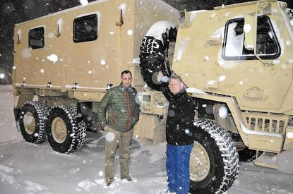 Howard County Emergency Management Director Ryan Miller, left, and County Executive Allan Kittleman stand by one of the vehicles provided by the National Guard on Friday night as Winter Storm Jonas brings heavy snow and winds to the area.