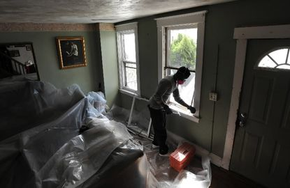 A worker replaces windows in older home to reduce risks of young children being exposed to lead paint dust and flakes.