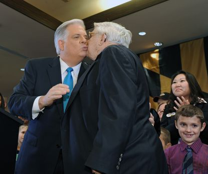 Msryland Governor-elect Larry Hogan, left, a Republican, kisses his father Lawrence Hogan Sr. during his victory party.