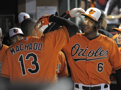 Orioles' Manny Machado (13) and Jonathan Schoop (6) exchange salutes after Schoop blasted a grand slam to break the game open against the Toronto Blue Jays during the sixth inning at Camden Yards on April 11, 2015.