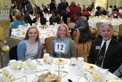 """Gerstell Academy ninth-grader Madeleine Bauhof sits with her mother, Tracy Bauhof, and Stephen Olzsewski at the Fox 45 """"Champions of Courage"""" breakfast at the historic Grand Hotel in Baltimore."""