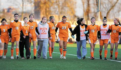 Members of the Fallston girls soccer team try to keep their heads up as the make their way across the field to receive their trophies after a 1-0 loss to Calvert in Saturday's 2A state championship game at Loyola University.