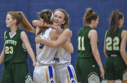 Liberty's Rachel Thiem, left, and Alex Bull embrace as time expires and the Lions defeat Century 64-45 to claim the Class 2A West Region I championship for the 2019-20 season.