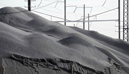 Amtrak's power lines rise above a mound of copper slag at the property of Opta Minerals, at 5800 East Fayette Ave., Baltimore.