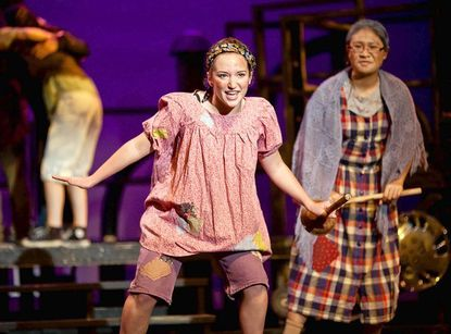 """Maddie Borowski dances with a plunger in her hand while playing her character """"Soupy Sue"""" in a dress rehearsal of Hammond's """"Urinetown: The Musical."""" At right is Janet Dabu, playing the part of """"Josephine Strong."""""""