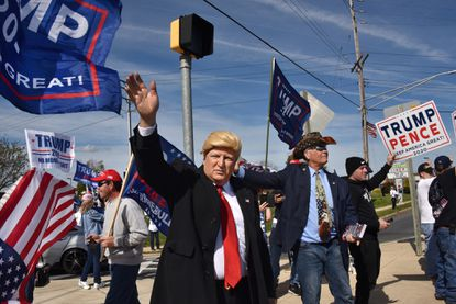 Michael Hess of Essex, dressed as President Donald Trump, with state Sen. Johnny Salling behind him, waves at drivers on Holabird Avenue at the culmination of a Trump car caravan organized by Baltimore County Republicans. The caravan of about 100 vehicles gathered at Eastern Regional Park in Middle River and traveled to the Boulevard Diner in Dundalk, where supporters gathered at the busy intersection of Merritt Boulevard and Holabird with flags and signs. Oct. 18, 2020.
