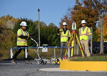 Lynnea Tapp, a geotechnical engineer at KCI Technologies, demonstrates an AM Gradiometer, which reads radio waves below the ground surface, as Charbel Khoury, center, a KCI practice leader, and Ron Dove, a senior project manager, look on.