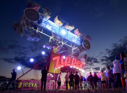 Carnival-goers line up to ride the Zipper on the opening night of the Gamber fire company carnival Friday, Sept. 3, 2021. The fire company will put on a fireworks show Sunday night with a rain date on Monday. The Carnival runs nightly from 6:00 - 11:30through Saturday, Sept. 11, however, it is closed on Wednesday, Sept. 8.
