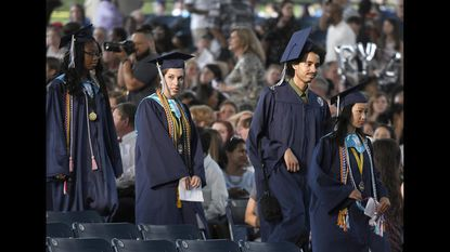 Howard High School seniors, including Desmond Lalli, second from right, walk in a procession at the start of the school's graduation ceremony at Merriweather Post Pavilion.