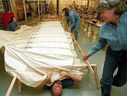 At the Wright Experience, a plane-restoration shop in Warrenton, Va., Greg Cone (on floor) places fabric on the wing panels of the 1903 Wright Flyer reproduction.