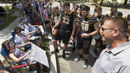 "Members of the Towson University football team, including head coach Rob Ambrose, right, sing ""Happy Birthday"" to Maya Libit, left, of Rodgers Forge, who turned 10 on July 4, during Towson's Fourth of July parade."