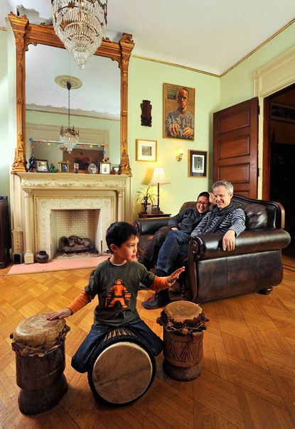 Hoa Tran, center, and Tendai Johnson, right, relax in the front drawing room with their 5-year-old son Fadzi Lai Tran Johnson.
