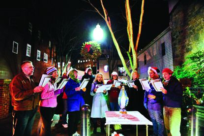 Carolers from various churches in Ellicott City sing Christmas songs during the Midnight Madness event in 2012.