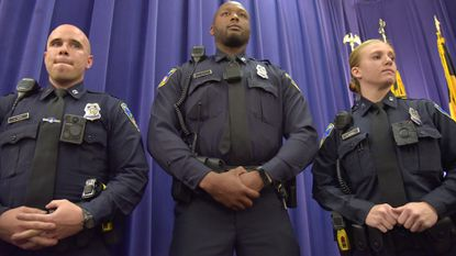 Baltimore Police officers Gregory Twigg, Alan Chanoine and Hanna Parrish wear three different body camera models that will be tested during a two-month pilot program that began Monday.
