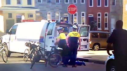 This image from a citizen video taken on April 12, 2015 shows Freddie Gray on the ground behind a police van. The driver of the van, Officer Caesar Goodson Jr. now faces more than 20 charges of violating police policies in his handling of Gray, who died a week after his arrest.